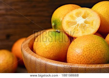 Closeup for ripe kumquat fruit in wooden bowl on wooden table