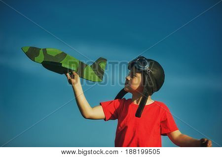 A happy child playing with a toy airplane. A dream of being a pilot
