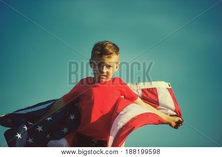 Happy boy with the American flag. Patriotic holiday. Flag of the USA