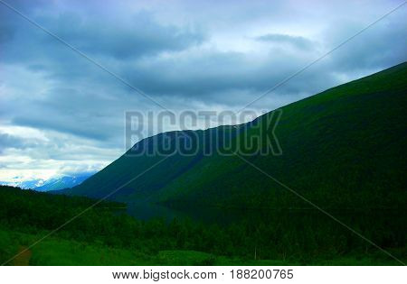 lake near green mountains on a cloudy summer day