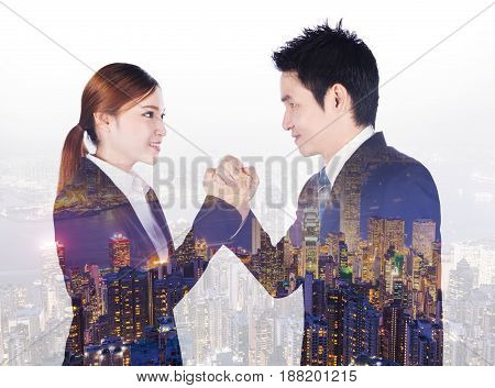 Double Exposure Of Arm Wrestling Between Businessman And Businesswoman With City Background