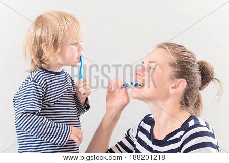 Mom with little cute baby brushing teeth