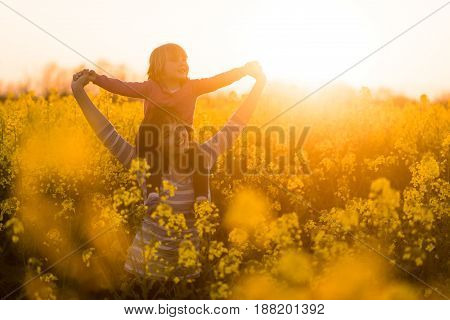 Joyous mother giving a ride to her child in the rapeseed field