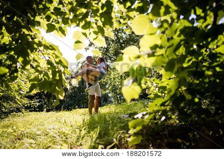 Young couple hugging and kissing among trees - photographed through leaves