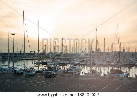VALENCIA SPAIN - FEBRUARY 3 2016: Evening at port of Valencia pier with a plenty of yachts and sunset with pink sky Valencia Spain.