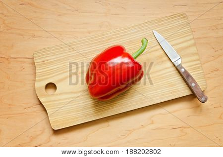 Juicy red pepper on the kitchen board. Clean Eating or Vegetarian concept. Overhead shot