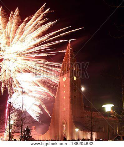 Reykjavík, Iceland, New Year Eve, Fireworks near Hallgrímskirkja - modern cathedral with striking belltower.