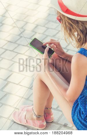 Girl using cellphone on the street on a sunny summer day.