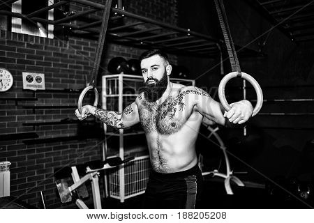 Young Muscular Bearded Tattooed Man With Naked Torso  Working Out His Muscles On Rings. Man Training