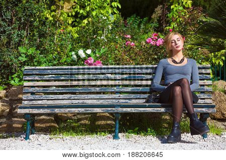 Waiting for love. Young girl in love on the bench. A beautiful young blonde girl sitting on a bench outdoors. Near plants and flowers. Romantic scene daylight.