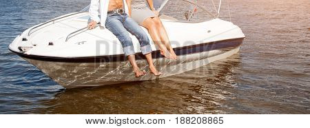 Legs hanging from the boat floating on the river. Love couple or friends relaxing on a yacht, enjoying sun on sunny summer day. Vacation holidays, romantic theme. Banner for website.