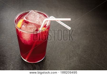 A photo of a vibrant glass of tinto de verano, traditional Spanish summer drink, on a black background with a place for text