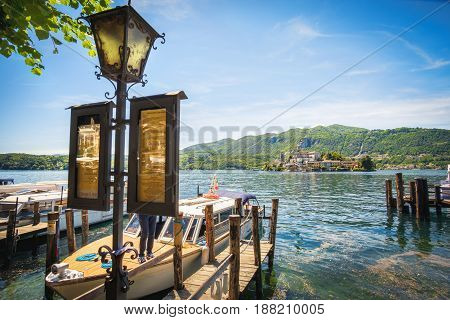 Orta San Giulio Italy 21 May 2017 - The Orta lake boat docks and lamppost with timetables to the San Giulio island