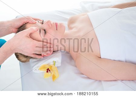 Beautiful young woman in a spa having a relaxing head massage from a therapist