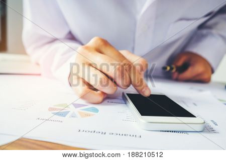 Business Man Using Smartphone For Online Banking On The Desk In The Office