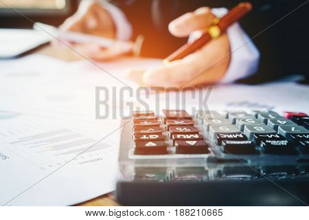Businessman's Hands With Calculator At The Office And Financial Data Analyzing Counting On Wood Desk