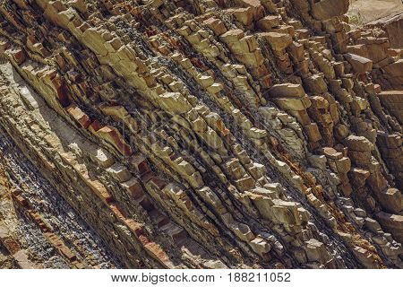 Ferric rock strata closeup. Rusty rock pattern and texture.