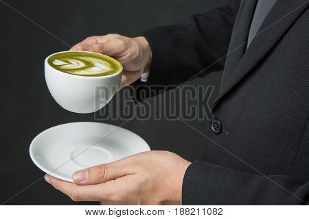hands of businessman holding a cup of coffee or green tea on grey background