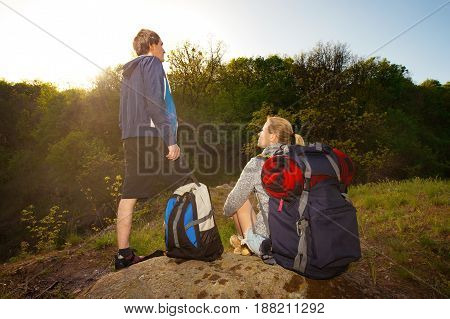 Man and woman hikers trekking in mountains. Young couple resting with backpacks in forest at sunset