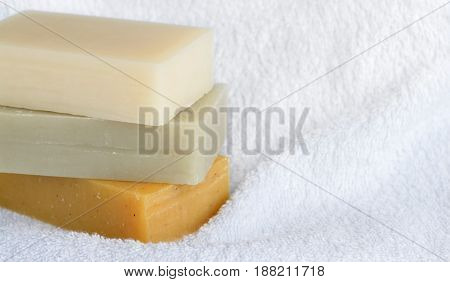 Natural homemade soaps on white bath towel background , shallow DOF