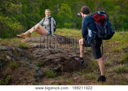 Young couple hikers resting. A man is taking photo of his girlfriend. Travel vacation holidays and adventure concept. Forest Mountain landscape background