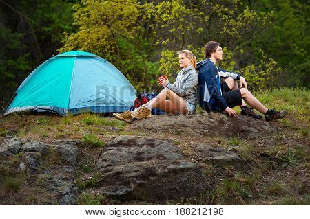 Couple hiking in the wild forest. Man and woman resting with cup of tea near the tent. Travel vacation holidays and adventure concept. Forest Mountain landscape background