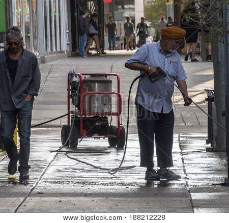Calgary Alberta/Canada - August 30 2015: A man pressure-washing a sidewalk outside of a business in Calgary Alberta.