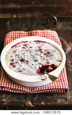 Traditional french pie clafouti with cherry and cranberry powdered with icing sugar in a baking pan on a wooden table, selective focus