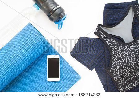 Overhead view of mobile device yoga mat yoga clothing and bottle of water on white background