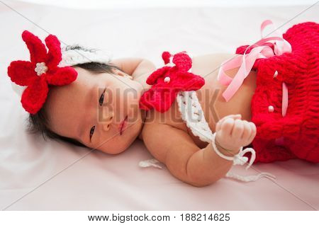 Focus at Asian newborn baby girl with costumes little mermaid in red color beside the window with sunlight
