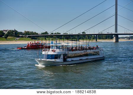 DUESSELDORF, GERMANY - AUGUST 17, 2016: A sightseeing and fire patrol boat cross their ways on river Rhine near Oberkasseler bridge