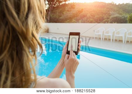 Girl using cellphone near swimming pool in the summer.