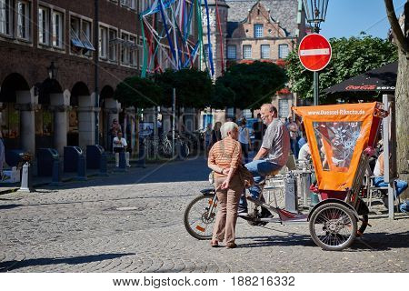 DUESSELDORF, GERMANY - AUGUST 17, 2016: Unidentified riksha driver chats with an unidentified lady in Duesseldorf Altstadt