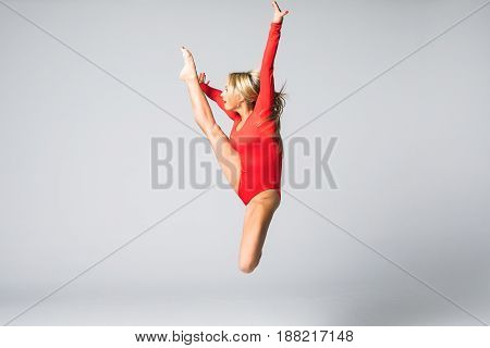 Young Beautiful Dancer In Red Swimsuit Posing On A Isolated White Studio Background