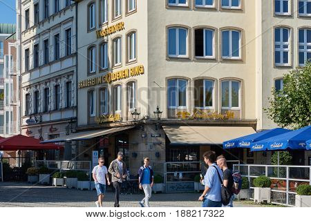 DUESSELDORF, GERMANY - AUGUST 17, 2016: Unidentified young men walk along a brewery pub at the Burgplatz in the Altstadt
