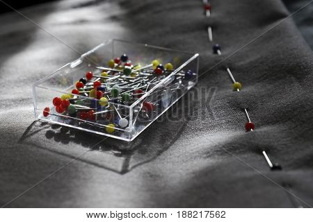 Plastic transparent box with sewing colored needles on a background of gray fabric. On the fabric of needles, a line of the future seam is drawn. Sewing accessories, weaving.