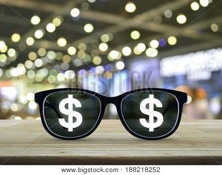 Dollar currency icon with eye glasses on wooden table over blur light and shadow of shopping mall Business success concept