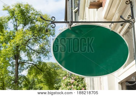 Old style wrought green iron hanging shop sign house. Free place for your text is on the blank hanging shop sign.
