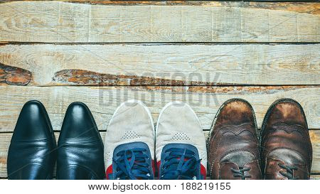 Three pairs of shoes on wooden backgriound: Busines shoes casual shoes and hiking boots Concept of choosing right footwear