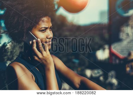 Serious beautiful young black lady trying to dial out via her smartphone to her mother in noisy park pensive afro american girl with curly hair calling to her boyfriend using cell telephone in garden