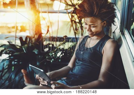 Smiling black curly teen sitting on the porch of resort summer house near pond and reading electronic book cheerful afro american girl in t-shirt is making selfie on digital tablet near house window
