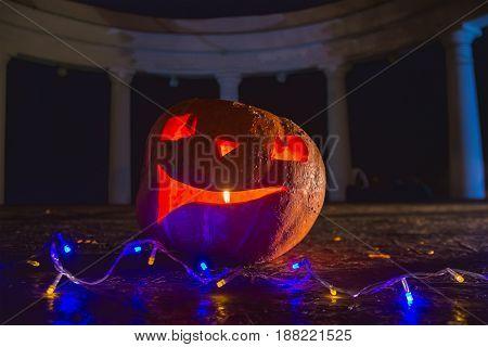 Halloween pumpkin at night park with garland