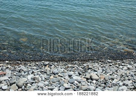 rocky beach of gray stones stretching into the sea