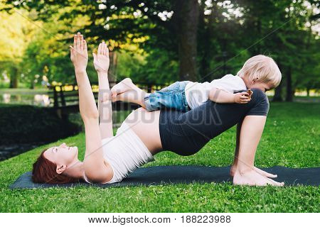Beautiful pregnant woman doing yoga with little son on nature outdoors. Mother and cute toddler child doing sports exercises together and have fun in summer park. Little yogi yoga kids.