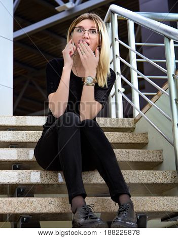 Pretty young woman looking shocked and surprised open mouth and eyes using smart phone sitting on stairs