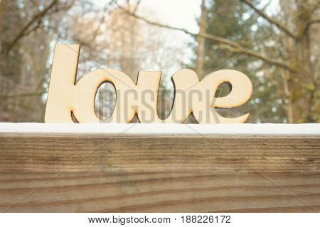 Abstract wooden love sign on wooden texture with snow in winter forest. Winter weather concept