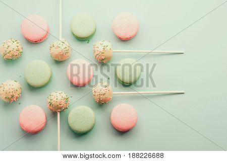 Flat lay of colorful macaroons with sweet cake pops on sticks. Top view