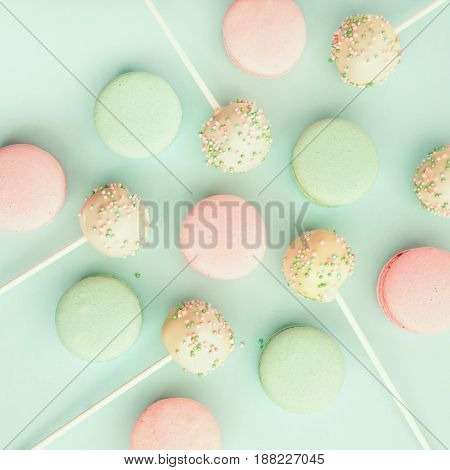 Colorful macaroons mixed with delicious cake pops. Top view. Flat lay
