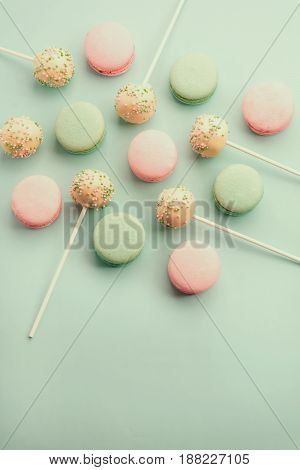 Colorful sweet macaroons mixed with sweet cake crumbs on sticks. Flat lay with copy space