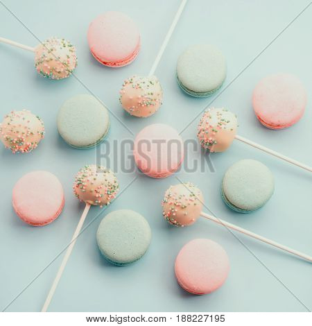 Colorful macaroons mixed with sweet cake crumbs with icing on sticks. Top view. Flat lay